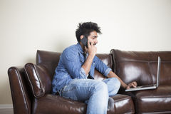Indian Man using a laptop and phone at home. Stock Photography