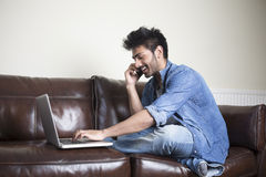Indian Man using a laptop and phone at home. Royalty Free Stock Photo