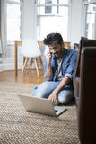 Indian Man using a laptop and phone at home. Royalty Free Stock Photos