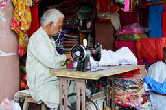 Indian Man using Sewing Machine at Market Royalty Free Stock Image