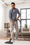 Indian man with vacuum cleaner at home. Household and cleaning concept - indian man with vacuum cleaner at home royalty free stock photos