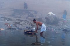 Indian man washes clothes in the holy water of the river Ganges at cold foggy winter morning. Varanasi Royalty Free Stock Photo