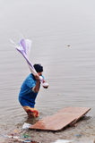 Indian man washes clothes in the holy water of the river Ganges in Varanasi Stock Image