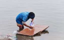 Indian man washes clothes in the holy water of the river Ganges in Varanasi Royalty Free Stock Photos