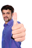 Indian Man Wishing Good Luck. An Indian guy wishing good luck with a thumbs up sign, on white studio background. Focus on hand Royalty Free Stock Photography