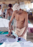 Indian man working hard on Dhobi Ghat in Cochin, India Royalty Free Stock Photo