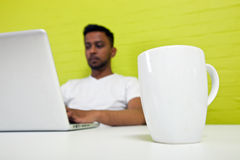 Indian man working at his desktop with mug in focus in foreground Stock Images