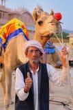 Indian mand standing with camel at Man Sagar Lake in Jaipur Stock Photo