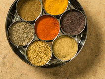 Indian masala box closeup. Photo of a Masala box containing turmeric, fenugreek, coriander, garam masala, black mustard seeds, red chilli, and cumin seeds Royalty Free Stock Images