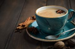 Indian masala chai tea. Spiced tea with milk on dark  wooden background. Indian masala chai tea. Spiced tea with milk on dark  wooden background, selective Stock Photography