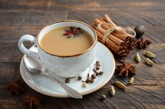 Indian masala chai tea. Spiced tea with milk on the rustic wooden table. Indian masala chai tea. Spiced tea with milk on the rustic wooden table, selective stock photography
