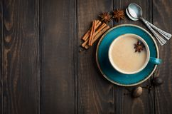 Indian masala chai tea. Spiced tea with milk on dark  wooden background. Indian masala chai tea. Spiced tea with milk on dark  wooden background, top view, copy Royalty Free Stock Photo