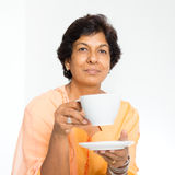 Indian mature woman drinking coffee. Portrait of a 50s Indian mature woman drinking coffee at home. Indoor senior people living lifestyle Royalty Free Stock Photography