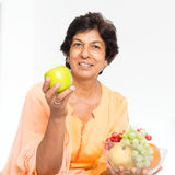 Indian mature woman eating fruits. Old people healthy eating. Portrait of a 50s Indian mature woman eating fruits at home. Indoor senior people living lifestyle Royalty Free Stock Photos