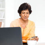Indian mature woman online shopping Royalty Free Stock Image