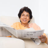 Indian mature woman reading newspaper Royalty Free Stock Images