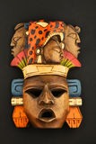 Indian Mayan Aztec wooden carved painted mask on black. Indian Mayan Aztec wooden carved painted mask with roaring jaguar and human faces isolated on black paper Royalty Free Stock Image