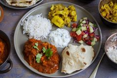 Indian sharing meal. Indian meal with chicken tikka masala, aloo gobi, raita, flatbreads and salad Royalty Free Stock Photography