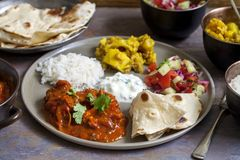Indian sharing meal. Indian meal with chicken tikka masala, aloo gobi, salad, rice and flat bread Royalty Free Stock Images