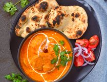 Indian Meal -Butter Chicken with roti and salad. Indian meal consisting of butter chicken curry as the main dish, along with Indian flatbread roti and Salad royalty free stock photo