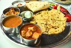 Indian Vegetarian Rajasthani thali. Indian Vegetarian meal consisting of Indian bread, curry, dry vegetable, salad, yogurt, dessert Stock Image
