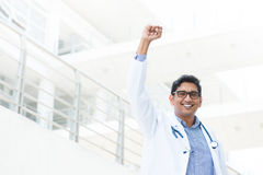Indian medical doctor celebrating success. Successful Asian Indian medical doctor with arm up celebrating his victory, hospital building as background stock images