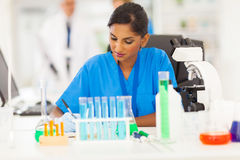 Indian medical researcher. Beautiful young indian medical researcher writing report in lab Royalty Free Stock Images