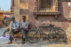 Indian men with bicycle on street stock photos