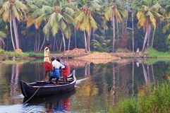 Indian men in a boat across the river. KOVALAM, INDIA - DEC 28, 2014: Unidentified Indian men in a boat across the river in a fishing village. Kovalam. Kerala Stock Photo