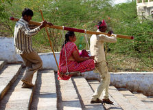 Indian men carry the palanquin with the old woman Royalty Free Stock Photography