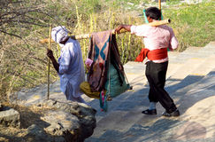 Indian men carry the palanquin with the old woman Stock Photo