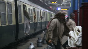 Indian men fastly taking metal containers out of arriving train. stock footage