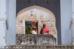 Indian men on the ghat along the sacred Sarovar lake. Pushkar - famous worship place in India Stock Photo