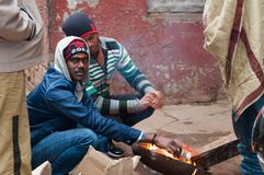 Indian men heating themselves at the fire at cold foggy winter morning. Varanasi Stock Image