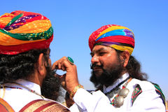 Indian men helping each other during Mr Desert competition, Jaisalmer, India. Indian men helping each other during Mr Desert competition, Jaisalmer, Rajasthan royalty free stock images