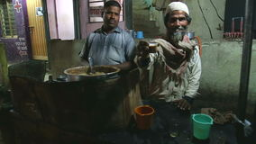 Indian men selling chai at a street stand in the night time in Mumbai.