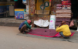 Indian men sew blanket near market on the street Royalty Free Stock Photography