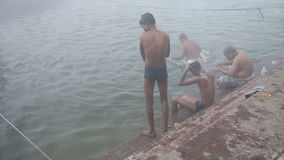Indian men showering in Ganges river in Varanasi. VARANASI, INDIA - 25 FEBRUARY 2015: Indian men showering in Ganges river in Varanasi stock footage