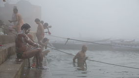 Indian men showering in Ganges river in Varanasi. VARANASI, INDIA - 25 FEBRUARY 2015: Indian men showering in Ganges river in Varanasi stock video footage