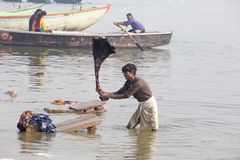 Indian men washes clothes in the holy water of the river Ganges at cold foggy winter morning. Varanasi. Uttar Pradesh, India stock photos
