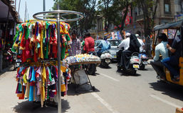 Indian merchant sell clothes on the pavement on a busy road Royalty Free Stock Photography