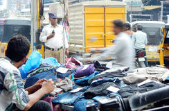 Indian merchant sell clothes on the pavement on a busy road Royalty Free Stock Image