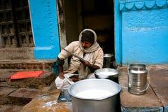 Indian milkman sells milk on the street. VARANASI, INDIA: Indian milkman sells milk on the street and read a newspaper the same time. Varanasi urban Stock Photos