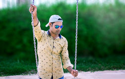 Indian Model standing in park holding swing chain Stock Photos