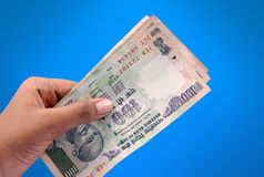 Indian money. Hand with indian money in blue background Stock Photo