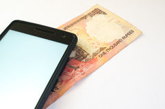 Indian money with mobile phone on white Royalty Free Stock Photo
