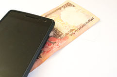 Indian money with mobile phone on white Royalty Free Stock Photos