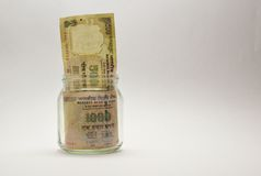 Indian Money or Rupee or currency or bank notes in glass jar Stock Photos