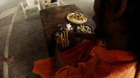 Indian monk in orange clothes ties big cotton wicks to light fixture