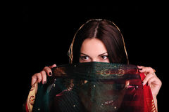 Indian mood. Beautiful young woman with a veil. Young caucasian dark-haired pretty woman hides a face behind a piece of Indian sari. Studio low key shot Royalty Free Stock Images